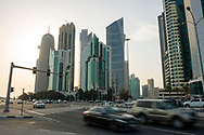 Cars travel on a major road at sunset in Doha, Qatar