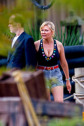 """EXCLUSIVE: Kirsten Dunst was spotted showing off her toned body while filming a pool scene for her AMC tv series """"On Becoming a God in Central Florida"""". Kirsten wore a bejewelled black swimsuit with high rise denim shorts, accessorising with hooped gold earrings and her hair tied back in a ponytail. She could be seen filming scenes with fellow actor Kevin J. O'Connor while a group of swimmers all run out past the two. The series, filming in Louisiana, is about """"Krystal Gill"""" (Dunst's character), a minimum-wage-earning water park employee who will eventually scheme her way up the ranks of Founders American Merchandise: the cultish, flag waving, multi-billion dollar pyramid scheme that drove her family to ruin. 19 Nov 2018 Pictured: Kirsten Dunst, Kevin J. O'Connor. Photo credit: MEGA TheMegaAgency.com +1 888 505 6342"""