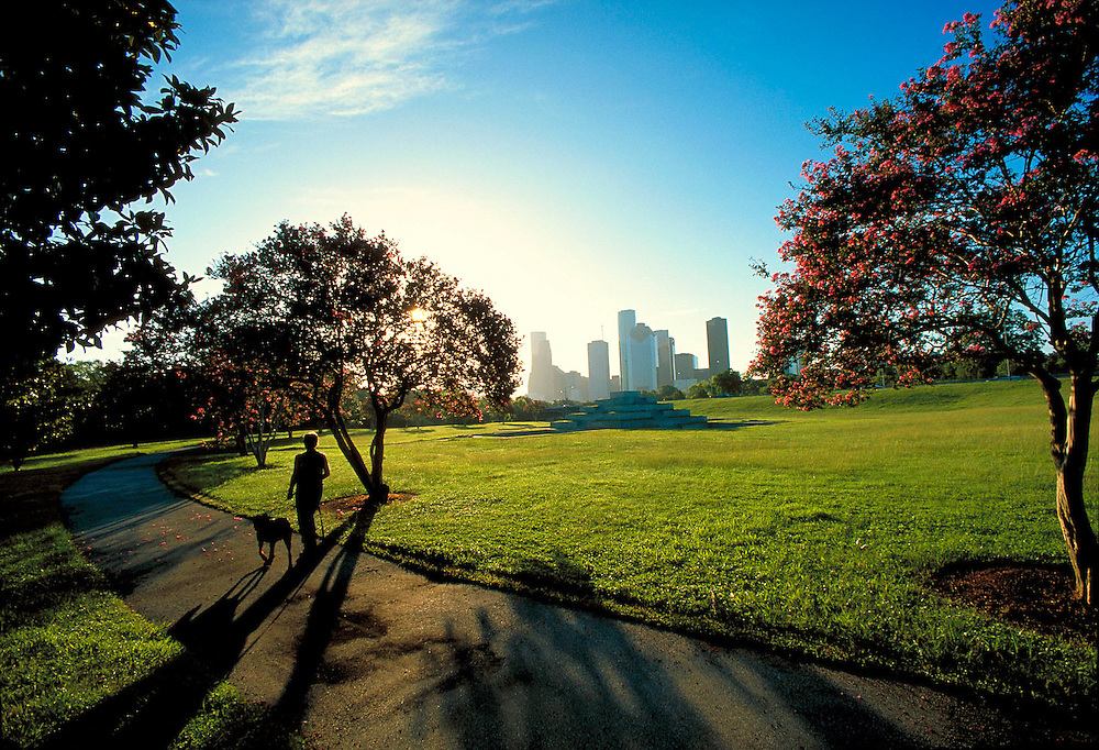 Stock photo of a person walking their dog past the Houston Police Officers Memorial, with the Houston downtown skyline in the background