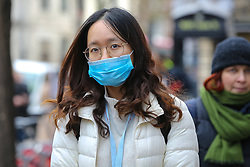 © Licensed to London News Pictures. 14/02/2020. London, UK. A fashion enthusiast wearing a surgical face mask arrives for the London Fashion Week shows in The Strand. The latest Coronavirus patient in London is linked to 'super spreader'attended transport conference with 250 people in Westminster. Photo credit: Dinendra Haria/LNP