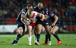 St Helens' Luke Thompson is tackled by Leeds' Brad Singleton and Jamie Jones-Buchanan during the Super League match at the Totally Wicked Stadium, St Helens.