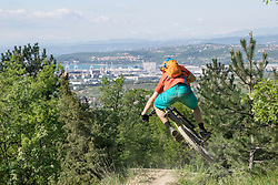 Rear view of mountain biker performing jump stunt on his bike