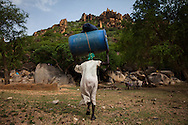 A woman carries supplies up to a cave where she was forced to flee after her villaged was bombed. Thousands of Nuban people have fled to caves to live after repeated bombing attacked by Sudan government forces on civilians areas.