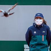 PARIS, FRANCE October 05. A pigeon flies around the court watched by a line judge at the start of the Laura Siegemund of Germany match against Paula Badosa of Spain in the fourth round of the singles competition on CourtSimonne Mathieu during the French Open Tennis Tournament at Roland Garros on October 5th 2020 in Paris, France. (Photo by Tim Clayton/Corbis via Getty Images)