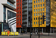 Yellow architecture and construction waste bins at St. Giles at the end of Denmark Street, on 4th March 2019, in London England.