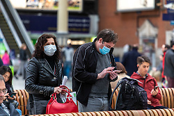 © Licensed to London News Pictures. 12/03/2020. London, UK. Train travellers at Victoria Station wear masks as the World Health Organization declares Covid19 the Coronavirus disease a Pandemic and US President Donald Trump bans all travel from Europe except the UK as fears over the Coronavirus continues. Photo credit: Alex Lentati/LNP