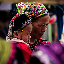 """Bac Ha Market, Lào Cai Province - Vietnam. Market Hmong Ethnic Groups<br /> <br /> The markets in North Vietnam offer great cultural diversity. Flower Hmong, White Hmong, Black Hmong, Thay, Thai or Dzao are selling their stuff on different days of the week. There are even backward markets, those markets are held every week one day back, so if this week's market is scheduled for Sunday, next week the market will be on Saturday, then Friday…A row of ambulant barbers is placed on the sidewalk and take care of their customers while shoppers flock around in search of new trends, tribal clothes or just their weekly grocery. Most of those markets have one thing in common, ethnic teenagers are dressing up to attract the other gender, since the size of the small communes and distances in between makes it hard for them to find the """"right one"""". Nevertheless in most cases the parents choose the """"right one"""". There are cows, puppies or birds changing ownership. Some market ladies reminded me on witch doctors offering their alternative medicine such as indefinable roots, dried mushrooms, wood bark or certain parts of fluffy animals. There is 3-5 years old rice wine waiting in jerrycans for shoppers to try and buy. As a highlight for the fancy dressed White Hmong a lot stack of colorful cloth is waiting."""