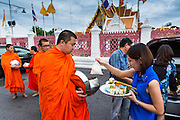 """21 JULY 2013 - BANGKOK, THAILAND:  A woman gives food to a monk and makes merit at Wat Benchamabophit on the first day of Vassa, the three-month annual retreat observed by Theravada monks and nuns. On the first day of Vassa (or Buddhist Lent) many Buddhists visit their temples to """"make merit."""" During Vassa, monks and nuns remain inside monasteries and temple grounds, devoting their time to intensive meditation and study. Laypeople support the monastic sangha by bringing food, candles and other offerings to temples. Laypeople also often observe Vassa by giving up something, such as smoking or eating meat. For this reason, westerners sometimes call Vassa the """"Buddhist Lent.""""       PHOTO BY JACK KURTZ"""