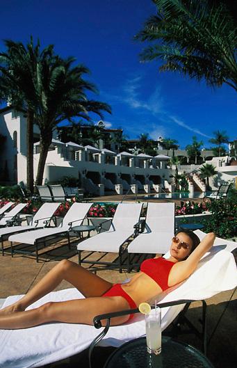 Woman in red bikini lies by pool at Baccara Hotel, Goleta, Santa Barbara, California,