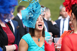 © Licensed to London News Pictures. 09/04/2016. Liverpool, UK. A woman in a brightly coloured dress and hat laughs with friends on Grand National day of the Grand National 2016 at Aintree Racecourse near Liverpool. The race, which was first run in 1839, is the most valuable jump race in Europe. Photo credit : Ian Hinchliffe/LNP