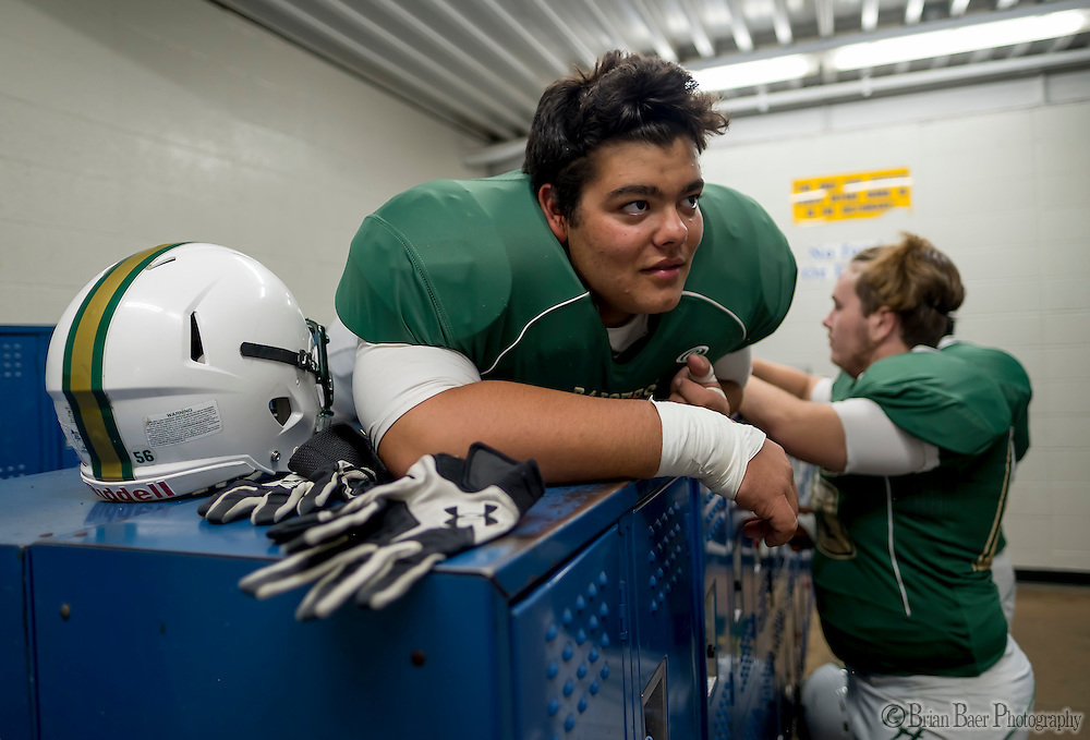 Rio Americano Raiders Ron Pile (77), lays on top of the lockers as he gets ready inside the locker room before the game as the El Camino Eagles host the Rio Americano Raiders at Del Campo High School, Friday Oct 7, 2016. <br /> photo by Brian Baer