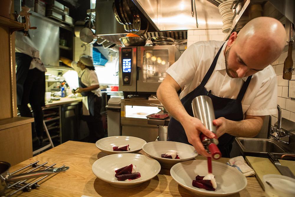 Owner-Chef Jose Ramirez-Ruiz at work in the kitchen of Semilla, plating beets with beef bone marrow.