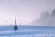 Commercial fishing boat in fog anchored in calm water near point land, Wm R. Hearst State Beach, San Simeon, California