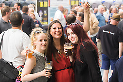Olympia, London, August 9th 2015. Hundreds of real ale lovers attend the Campaign for Real Ale  Great British Beer Festival at London's Olympia Exhibition Centre, where dozens of independent breweries demonstrate the diversity of British brewed beers. PICTURED: Three friends enjoy the festival atmosphere.