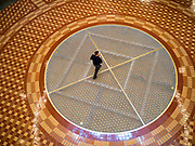 "16 MARCH 2020 - DES MOINES, IOWA: A person walks through the empty rotunda in the State Capitol in Des Moines. Because of numerous reports of Coronavirus in Iowa, the governor is suspending the legislative session for 30 days. It was scheduled to run until mid-April. Sunday night, the Governor announced that the state health department had recorded ""community spread"" in Des Moines. As a result the State Capitol instituted mitigation measures that included mandatory health screening for everyone going into the building, canceling group tours of the building, and closing the souvenir shop and snack bar.     PHOTO BY JACK KURTZ"