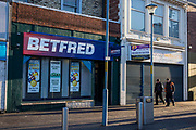 A Betfred betting shop Middlesborough town centre, North Yorkshire, United Kingdom.  This is a poor and deprived area of the city and shop unit next to the shop is empty and for sale by action.