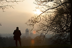 © Licensed to London News Pictures 02/03/2021. Greenwich, UK. A woman watching the sunset. People get out of their homes from a third national Coronavirus lockdown to enjoy the sunset in Greenwich Park, London. Photo credit:Grant Falvey/LNP