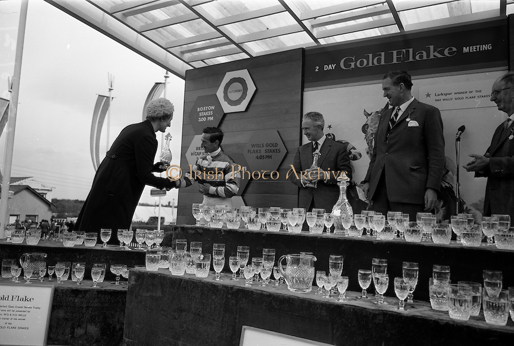 08/05/1965<br /> 05/08/1965<br /> 08 May 1965<br /> The 1965 Gold Flake Meeting at Leopardstown Racecourse, Co Dublin. Image shows Mrs D.R. Mott, wife of the Managing Director of Wills of Dublin and Cork, presenting the set of Waterford Glass to the winning jockey, Jack M. Purtell in the Gold Flake Stakes. Also in the picture are Mr Vincent O'Brien, Trainer, Mr D.R. Mott and Mr Fred Clarke, Managing Director of Leopardstown Club. Note the Waterford Glass Crystal Service sets presented to the winning owner, trainer and jockey.