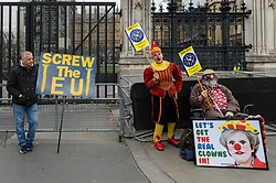 March 27, 2019 - London, Greater London, United Kingdom - Pro-EU supporters dressed as clowns with a placard depicting Theresa May stand next to an anti-EU protester outside the Houses of Parliament in London on 27 March, 2019. Today, MPs held a series of indicative votes on alternative Brexit plans following a government defeat in the Commons as parliamentarians took control of the order paper. (Credit Image: © Wiktor Szymanowicz/NurPhoto via ZUMA Press)