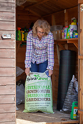 Moving fresh bags of compost into the shed for storage