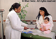 doctor, physician at work African American Female Pediatrician, Hispanic Mother and Baby, Urban Clinic