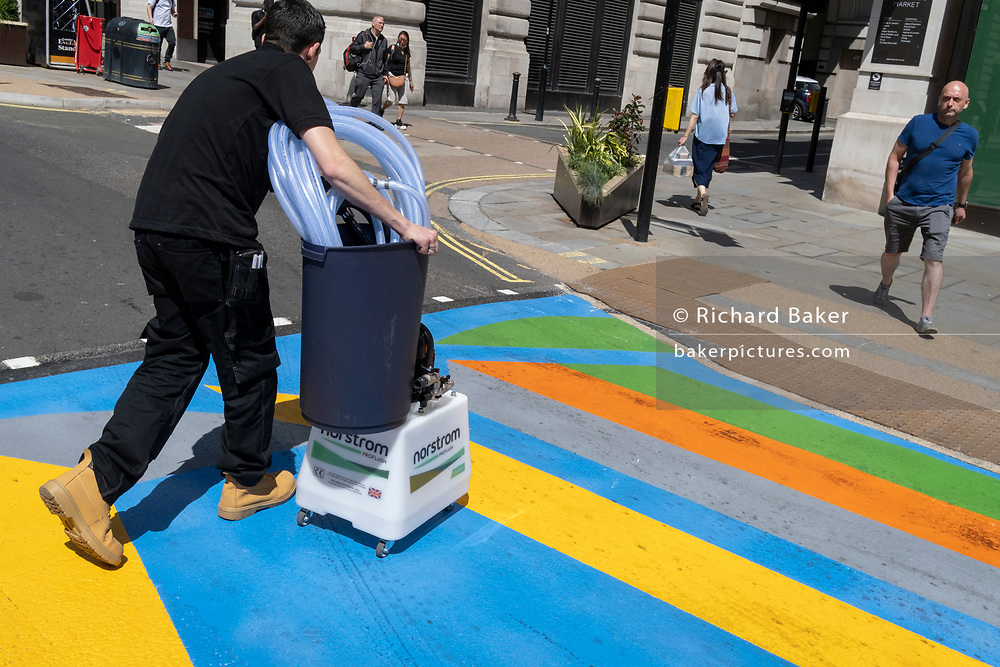 A wokman pushes a Norstrum Proflush over the multi-coloured markings of a crossing at Lower Regent Street, on 16th July 2021, in London, England.