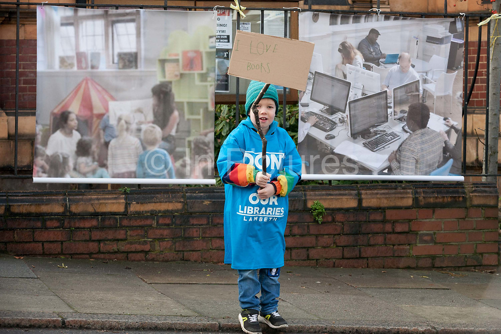 A young boy protests outside Carnegie Library on Herne Hill in south London which re-opens for the first time in almost 2 years, on 15th February 2018, in London, England. Closed by Lambeth council and occupied by protesters for 10 days in 2016, the library bequeathed by US philanthropist Andrew Carnegie has been locked ever since because, say Lambeth austerity cuts are necessary. A gym that locals say they dont want or need has been installed in the listed basement and actual library space a fraction as before and its believed no qualified librarians will be present to administer it. Protesters also believe this community building will ultimately sold off by Lambeth council for luxury homes.