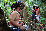 Chief Almir Narayamogo, with his apple computer, the other holds a gps reciever, they are mapping in the Surui territory, primary rainforest interior.<br /> <br /> An Amazonian tribal chief Almir Narayamogo, leader of 1350 Surui Indians in Rondônia, near Cacaol, Brazil, with a $100,000 bounty on his head, is fighting for the survival of his people and their forest, and using the world's modern hi-tech tools; computers, smartphones, Google Earth and digital forestry surveillance. So far their fight has been very effective, leading to a most promising and novel result. In 2013, Almir Narayamogo, led his people to be the first and unique indigenous tribe in the world to manage their own REDD+ carbon project and sell carbon credits to the industrial world. By marketing the CO2 capacity of 250 000 hectares of their virgin forest, the forty year old Surui, has ensured the preservation, as well as a future of his community. <br /> <br /> In 2009, the four clans and 25 Surui villages voted in favour of a total moratorium on logging and the carbon credits project. <br /> <br /> They still face deforestation problems, such as illegal logging, and gold mining which causes pollution of their river systems