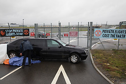 Farnborough, UK. 2nd October, 2021. An Extinction Rebellion climate activist lies locked to a stretch limousine blocking an entrance to Farnborough Airport. Activists blocked three entrances to the private airport to highlight elevated carbon dioxide levels produced by super-rich passengers using private jets and 'greenwashing' by the airport in announcing a switch to sustainable aviation fuel (SAF).