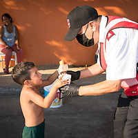 A Major from the Salvation Army hands a cream bun and hot chocolate to one of hundreds of children they feed twice a week in a camp of asylum seekers in Tijuana, Mexico.