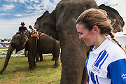 "28 AUGUST 2013 - HUA HIN, PRACHUAP KHIRI KHAN, THAILAND:  AMANDA SILLARS of the Citibank team, walks past her elephant at the King's Cup Elephant Polo Tournament in Hua Hin, Thailand. The tournament's primary sponsor in Anantara Resorts and the tournament is hosted by Anantara Hua Hin. This is the 12th year for the King's Cup Elephant Polo Tournament. The sport of elephant polo started in Nepal in 1982. Proceeds from the King's Cup tournament goes to help rehabilitate elephants rescued from abuse. Each team has three players and three elephants. Matches take place on a pitch (field) 80 meters by 48 meters using standard polo balls. The game is divided into two 7 minute ""chukkas"" or halves. There are 16 teams in this year's tournament, including one team of transgendered ""ladyboys.""    PHOTO BY JACK KURTZ"