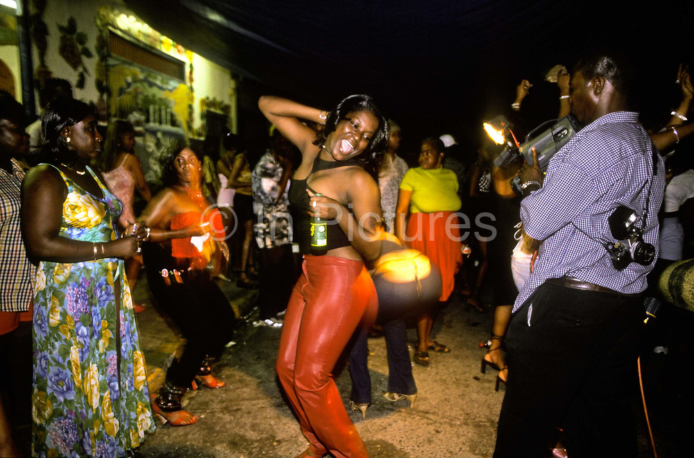 Women dance on the streets of Kingston to all night Dancehall. A very sexualized style of dancing, Jamaica.