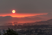 Looking west across San Francisco Bay looking over Point Richmond as the sun sets through wildfire smoke over the Marin Headlands, south of the Sonoma and Napa wildfires. Air quality on this day was rated as bad in San Francisco as in Beijing China. 12th October, 2017.