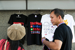 "© Licensed to London News Pictures. 05/01/2014. A vendor sells ""Shutdown Bangkok"" T-shirts to a protestor during the third day of the 'Bangkok Shutdown' as anti-government protesters continue with their 'shutdown' of Bangkok.  Major intersections in the heart of the city have been blocked in their campaign to oust Prime Minister Yingluck Shinawatra and her government in Bangkok, Thailand. Photo credit : Asanka Brendon Ratnayake/LNP"