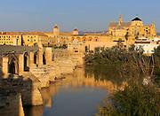 Roman bridge spanning river Rio Guadalquivir leading to the cathedral buildings, Cordoba, Spain