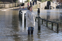 © Licensed to London News Pictures. 19/01/2014. A woman standing in flood water. The town of Eynsford in Kent flooded where the river Darent has broken it's banks after overnight rain caused river levels to rise. Photo credit :Grant Falvey/LNP
