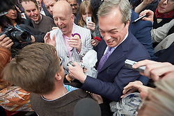 © Licensed to London News Pictures.  30/04/2015. AYLESBURY, UK. Nigel Farage (centre right), UKIP party leader, receives a gift from a supporter during a campaign visit to Aylesbury. <br /> <br /> Also in this picture: Chris Adams (centre left in light jacket), UKIP candidate for Aylesbury.<br /> <br /> Photo credit: Cliff Hide/LNP