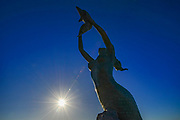 Mermaid and dolphins sculpture along the Malecon, evening light, February, La Paz, Baja, Mexico