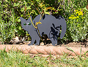 Black metal cat scarer in garden with green glass eyes to deter cats, UK