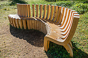 """Artfully curved wood bench in Roseg Valley, Engadine, Switzerland, Alps, Europe. Hike from Pontresina up Roseg Valley to Fuorcla Surlej for stunning views of Piz Bernina and Piz Rosegg, finishing at Corvatsch Mittelstation Murtel lift. Walking 14 km, we went up 1100 meters and down 150 m. Optionally shorten the hike to an easy 4 km via round trip lift. Pontresina is in Upper Engadine, in Graubünden (Grisons) canton, Switzerland. The Swiss valley of Engadine translates as the """"garden of the En (or Inn) River"""" (Engadin in German, Engiadina in Romansh, Engadina in Italian)."""