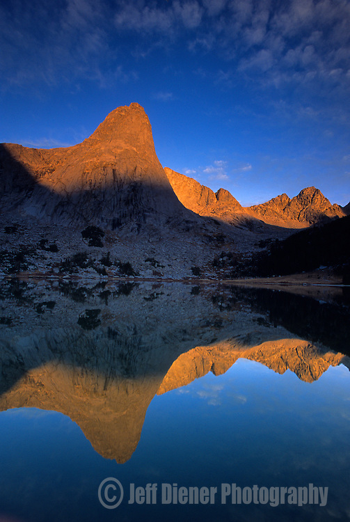 The calm waters of Lonesome Lake mirror the glowing peaks of the Cirque of the Towers, Wind River Range, Wyoming.