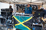 DJ at I Spy The People sound system on Colville Gardens. Notting Hill Carnival in West London. A celebration of West Indian / Caribbean culture and Europe's largest street party, festival and parade. Revellers come in their hundreds of thousands to have fun, dance, drink and let go in the brilliant atmosphere. It is led by members of the West Indian / Caribbrean community, particularly the Trinidadian and Tobagonian British population, many of whom have lived in the area since the 1950s. The carnival has attracted up to 2 million people in the past and centres around a parade of floats, dancers and sound systems.