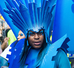 London, August 28th 2016. Resplendent in her blue head dress, a woman poses for the camera during Family Day at Europe's biggest street party, the Notting Hill Carnival.