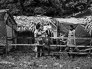 26 JANUARY 2018 - SANTO DOMINGO, ALBAY, PHILIPPINES: Evacuees from the Mayon Volcano living in tents at Barangay Lidong shelter get water from a tap near a school agricultural project. The shelter is in school and all of the classrooms are already being used to house evacuees. Recent arrivals are living in tents on the school grounds. The volcano was relatively quiet Friday, but the number of evacuees swelled to nearly 80,000 as people left the side of  the volcano in search of safety. There are nearly 12,000 evacuees in Santo Domingo, one of the communities most impacted by the volcano. The number of evacuees is impacting the availability of shelter space. Many people in Santo Domingo, on the north side of the volcano, are sleeping in huts made from bamboo and plastic sheeting. The Philippines is now preparing to house the volcano evacuees for up to three months.      PHOTO BY JACK KURTZ