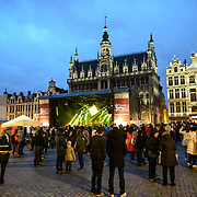 """The Belgian band Opmoc plays on a stage at the Brussels Jazz Marathon in the Grand Place, Brussels. Originally the city's central market place, the Grand-Place is now a UNESCO World Heritage site. Ornate buildings line the square, including guildhalls, the Brussels Town Hall, and the Breadhouse, and seven cobbelstone streets feed into it. In the background, behind the stage, is the Maison du Roi (or Broodhuis / """"Bread House"""") which houses the Museum of the City of Brussels."""