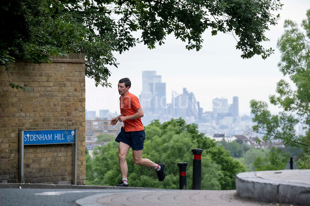 With the skyscrapers of the City of London, the capitals financial district, in the distance, a runner crosses Sydenham Hill, on 15th June 2021, in south London, England.