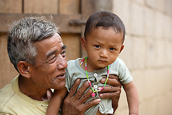 Thonglay 58 years old with his grandson Air. Grandparents play a vital part within the community handling childcare  People gather for an Older People's Group meeting where they will discuss individual and group needs.  <br /> Had Yen Village, Pakseng District, Luang Prabang Province, Lao PDR