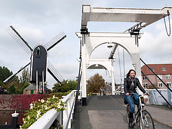 old bridge over canal and windmill in centre of Leiden in The Netherlands