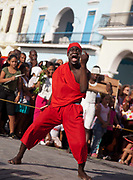 Cuban young man boy of African descent dancing, and waving a stick  and shouting, as part of a performance. Performance in Havana old town, local dance and theatre group enacting the slave trade, colonial rule and how African religion and beliefs continuing, becoming what is now Santeria.
