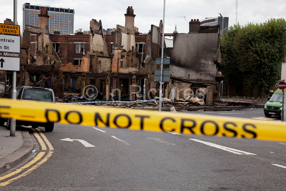 The burnt out remains of two furniture businesses at Reeve Corner in Croydon. The day after rioting took place in Croydon in South London. Riots flared for a third night in a row, resulting in burnt out buildings, looted shops and general smashed up devastation.